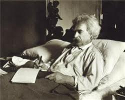 Mark Twain writing in bed
