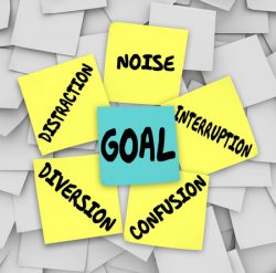 33251232 - goal word on sticky note surrounded by distractions, diversions, confusion, interruptions, and noise to keep you from accomplishing your mission or objective