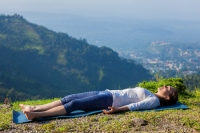 54728563 - woman relaxes in yoga asana savasana - corpse pose outdoors in himalayas. himachal pradesh, india