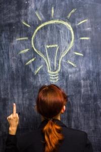 21561775 - redhead businesswoman at blackboard having bright idea