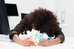 25337109 - distraught writer or businesswoman with her head lying on her desk in a pile of crumpled paper as she suffers from writers block or a total inability to come up with a solution to a problem