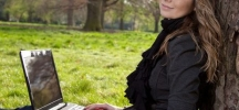 happy woman writing in park prayer answered